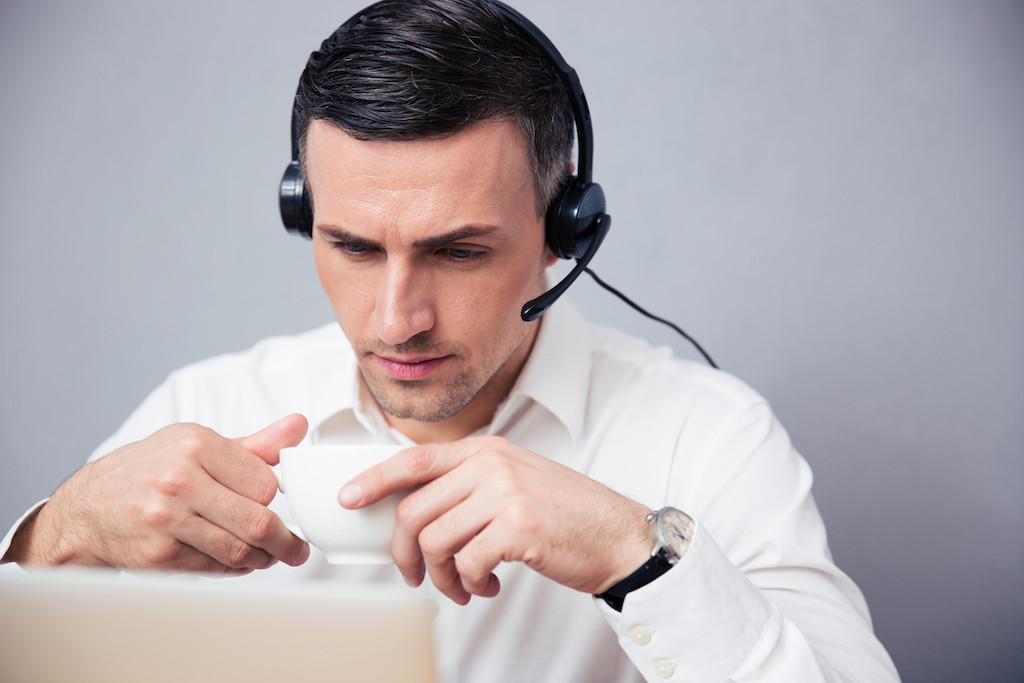 Businessman in headphones drinking coffee