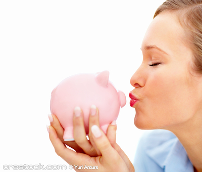 Pretty young female kissing piggybank and  cop...