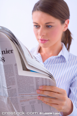 Young woman reading daily newspaper